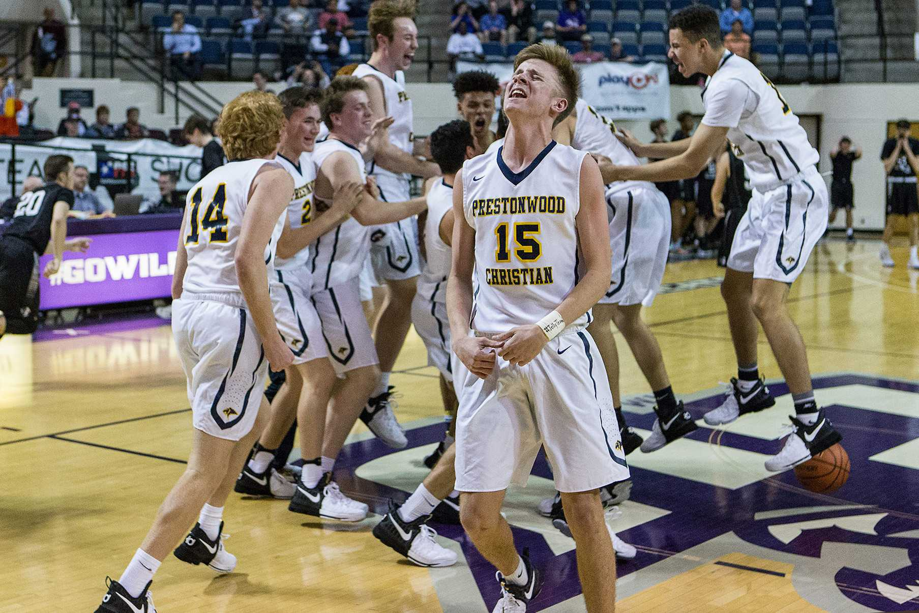 Junior Beck Atkins and the rest of the Varsity Boys Basketball team celebrate mid-court after winning their sixth TAPPS Division 1 State Championship in a row. The team defeated district rival Bishop Lynch, 45-42.