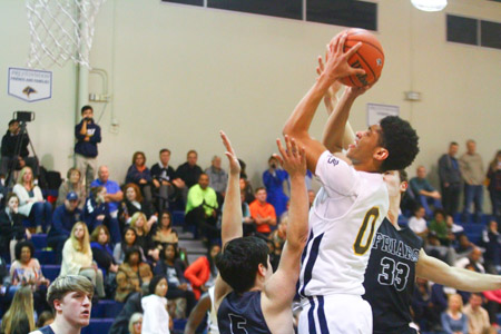 Junior Justin Webster goes up for the basket against Bishop Lynch. The Lions went on to win, 56-54.