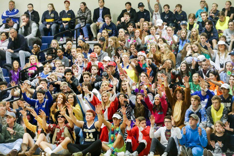 The brightly-colored student section holds hands up waiting for the free throw.
