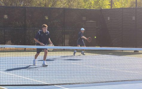 Doubles team Cole Trammel (11) and Travis Pratt (12) transition and hit the return in their match against John Paul II.