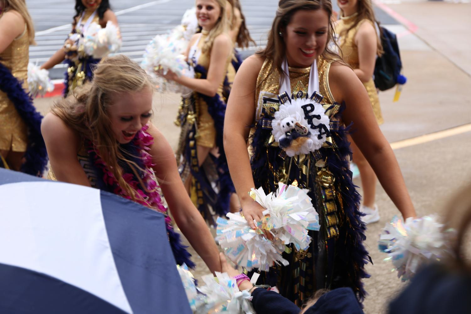 Isabelle Simpson (11) and Emma Stephens (10) greet excited Lower School students at the Homecoming Parade.