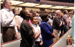 Students and their grandparents perform the pledges together at all school worship.